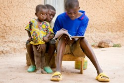 Siaka Diallo's brothers look on as he does his homework. Siaka, 16, started school late and has had only minimal basic education. He now attends the village's Non-Formal Basic Education Centre (CEBNF). The CEBNF provides out of school adolescents aged 9-15 with a second chance at education and the opportunity to learn a trade. Siaka spends the first hour at school every morning learning basic literacy and numeracy. These provide the foundation for the vocational training workshops where he spends the rest of his day, in Siaka's case, learning to be a tailor. The CEBNF is one of three schools in Sokoroni village. Along with the primary school and an early childhood development centre (Bisongo), they constitute Sokoroni's 'education complex'. A UNICEF-led approach to education, education complexes like the one in Sokoroni are helping an increasing number of villages in Burkina Faso to achieve Education for All.