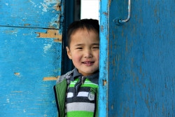 A boy smiling as he exits a UNICEF-supported school dormitory in Khatgal soum, Khuvsgul province as a part of WaSH interventions