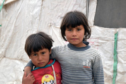Haya, 3, (left) and Sabeen, 5, (right) outside the shelter where they live