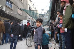 Local residents, including children, queue for aid delivered by a joint UNICEF, United Nations and Syrian Arab Red Crescent convoy of 46 trucks, which brought in food aid for 27,500 people, as well as health and nutrition supplies, in Douma, Eastern Ghouta, Syrian Arab Republic, Monday 5 March 2018. UNICEF continues to support children in need across Syria where there are 5.3 million children in need of assistance. Nearly 2 million children live in besieged and hard to reach areas, deprived of their basic rights and of getting assistance. The last convoy to reach Douma with humanitarian assistance was on 15 November 2017.