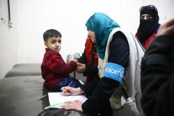 子どもの栄養状態を検査するユニセフのラジャ・シャーハン栄養専門官。(2018年3月15日撮影)
