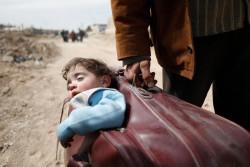スーツケースで子どもを運び、避難する男性。(2018年3月15日撮影)