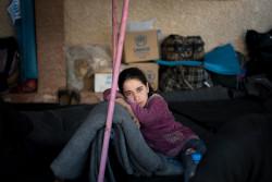 避難先の学校で、ブランケットにもたれかかる女の子。(2018年3月20日撮影)
