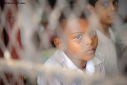 "On 13 March 2018 in Saif Ben Thei Yazan, Aden City, Yemen, a student attends class. Nearly half a million children have dropped out of school since the 2015 escalation of conflict in Yemen, bringing the total number of out-of-school children to 2 million.  Almost three quarters of public school teachers have not been paid their salaries in over a year, putting the education of an additional 4.5 million children at grave risk. According to the UNICEF report, ""If Not In School"", more than 2,500 schools are out of use, with two thirds damaged by attacks, 27 per cent closed and 7 per cent used for military purposes or as shelters for displaced people."