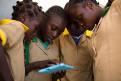 "Twelve-year-old Waibai Buka (second left) teaches her friends how to use a computer tablet provided by UNICEF, at a school in Baigai, northern Cameroon, Tuesday 31 October 2017. Waibai had to flee her village after an attack by Boko Haram. She has not seen her father since the attack and fears he might be dead. UNICEF initiated a pilot project in January 2017 called 'Connect My School'. Six solar-powered VSAT units, which enable the provision of satellite Internet access to remote locations, were deployed at schools in different parts of Cameroon. Two of the units were installed in schools in Cameroon's Far North region: one in Minawao refugee camp, the other in Baigai, near the Nigerian border, where some 50% of children have been displaced by Boko Haram related violence.  In conjunction with the VSAT units, UNICEF has distributed child-friendly tablet computers. Through these tablets, children are able to access Wikipedia and play educational games to help them learn maths, history, geography, and so on. As of November 2017, some 2,000 children in the 5th grade have benefitted from the initiative. ""I immediately started using them to search new words, play new games. I became so good at it that I now teach other children how to use this technology"" says Waibai, ""I was recently allowed to bring one of the tablets home with me. My mother never had a mobile phone, she didn't know what the Internet was. I explained her and I showed her what I was doing at school with my tablet. She was so proud of me.""  ""I think that we are lucky to have this technology,"" adds Waibai, ""my dream is to become a teacher, and with what I am learning every day on my tablet, I am sure it can become a reality."""