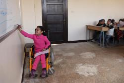 シリア・アレッポの学校に通うハナアちゃん(8歳)が、授業中にホワイトボードに書かれた問題を解いている。ハナアちゃんは、爆弾の爆発を受けて両足が不自由になった。(2018年2月28日撮影)