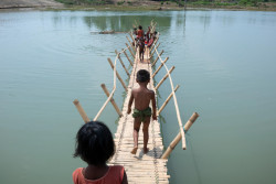 Rohingya children from Myanmar play on a bamboo bridge crossing a shallow body of water at high tide in Shamlapur refugee camp, Cox's Bazar District, Bangladesh on 19 April 2018. The Shamlapur camp, which sits just above the high tide line and extremely close to the open sea, is particularly susceptible to violent storms. Since an outbreak of violence began on 25 August 2017, hundreds of thousands of Rohingya people have sought refuge in neighboring Bangladesh. UNICEF and partners are working to provide for the needs of this enormous refugee population who will be all the more vulnerable during the upcoming monsoon and cyclone seasons.