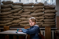 "Lera Nagormay, 10, sits for a photograph in a classroom at school in Marinka, Donetsk Oblast, Ukraine, Wednesday 22 November 2017. When conflict broke out in 2013, Marinka was heavily contested. ""One time, when I walked to school"" Lera says, ""when I arrived all the kids were already in the shelter. Shelling had started while I was on my way, and I had to rush in there.  The school still has weekly drills, corralling students into the bunker beneath the building. In a long cold room, seats line one wall for the smaller children.  ""Sometimes we bring our toys down here so we don't get bored waiting,"" Lera says. Today, a police officer wearing camouflage and armed with a rifle stands guard in the lobby of the school. After one child was shot in the arm in the playground, children are not permitted to play outside. Field trips are out of the question due to the risk posed by mines and unexploded ordnance. ""We have to stay inside the school all the time, and are not allowed to play outside during the breaks. The boys play football in the school's corridors"" Lera says, ""they can't break the windows because of the sandbags."" As of December 2017, the situation in eastern Ukraine remains volatile, and violence continues despite the latest ceasefire agreements committed on 19 July 2017. The lives of children and their families, especially those living along the contact line continue to be at risk. According to a December 2017 report by the United Nations Office for the Coordination of Humanitarian Affairs, millions of people are continuing to suffer unnecessarily due to the entrenched political impasse and the ongoing armed conflict. Despite many attempts at a ceasefire, hostilities continue with almost daily shelling, frequent localized clashes, and rapidly escalating mine and unexploded ordinance contamination.  The conflict has taken a severe toll on the education system, affecting students, teachers, administration and education facilities, hundreds of which hav"