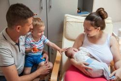 赤ちゃんに母乳を与える母親を見守る家族(セルビア)。(2017年6月撮影)