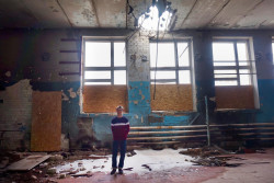 Oleksandr, 16 years old, is photographed in a gym of School in Troitske Luhansk region, that was directly hit by a shell. The gym is now used as a storage room.
