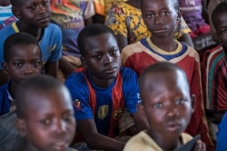 "Jospin sits in a class at the MINUSCA site in Kago Bandoro, Central African Republic, Monday 6 November 2017. ""I think I am 13,"" says Jospin, ""but my birth certificate was lost when they burnt my house. I am from a village 17 kilometres away on the road to Kabo. Three-years ago we left the village on foot, my father, my mother, my seven brothers and sisters and myself. We stayed on the church site, then MINUSCA when the church site was attacked. Actually it is as an IDP that I started going to school for the first time and I love it. I am in third grade now. I have decided to become a doctor because once I was sick and I went to the hospital and this big man, the doctor, treated me. He was very kind. So I have decided to become a doctor too, so I can help my people one day."" As of October 2017, violent clashes and inter-communal tensions fuelled by armed groups have continuously increased in the Central African Republic (CAR). In the absence of an effective judicial system and basic security services by the public administration, armed groups have continued to perpetrate violent and destabilizing acts, of which the civilian population is the main victim. The targeting of minorities, including women and children, has resurfaced, with killings and attacks against communities multiplying. Conflict and forced displacement is increasingly widespread and impacting previously unaffected parts of the country. As the crisis further expands towards the southeast and northwest of the country, there are new displacements and there is a significant risk that the condition of people previously displaced that remain in camps will deteriorate. Nearly one family out of four has already been forced to flee or seek refuge in neighbouring countries. While the official opening of the 2017–2018 school year kicked off on 18 September, many schools remain closed in areas where violence and insecurity persists. According to the Ministry of Education, over 170,000 children had not sta"