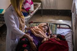 生後3日の赤ちゃんに寄り添う、母親のハゼラ・ベグムさん(18歳)。コックスバザールのロヒンギャ難民キャンプに設置されたユニセフの支援施設で、助産師の健診を受けている。(2017年10月撮影)