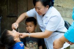 Nam Poung村を訪れたデンさんが、家の外で2人の男の子にポリオの予防接種をしている。チームが各家庭をまわって、拠点に来ずに予防接種を受けていない子どもたちを見つけ出した。