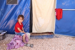 On 17 May 2018 in the Syrian Arab Republic, a girl sits outside a temporary shelter in Fafin tented camp. Too afraid to go back home in Afrin and not allowed to proceed to Aleppo city to reunite with family members and seek services, thousands of families are left living in inadequate conditions as the hot summer months approach. In May 2018 in the Syrian Arab Republic, more than 137,000 people from Afrin district have been displaced by escalating violence since 20 January 2018. Many remain displaced after several months, mainly in Tal Refaat, Nubul, Zahraa and surrounding villages north of Aleppo city. Many have left most belongings behind. Once well-off families are now sheltering in makeshift shelters, damaged or unfinished buildings, mosques, warehouses and open-spaces. Some 3,500 people are being accommodated in a tented camp in Fafin to the north of Aleppo. UNICEF has reached almost 35,000 children in collective shelters and makeshift camps with recreational activities and psycho-social support. Mine Risk Education sessions for children and caregivers have also been provided. Specialized case management is provided where needed, while more than 6,800 children received lifesaving nutrition services, including treatment for acute malnutrition.  Approximately 85,000 children will receive summer clothing kits over the coming weeks.