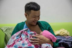 生まれたばかりの赤ちゃんを抱き、笑顔になるソンポンさん。(タイ) 2018年3月8日撮影
