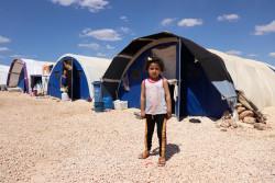 難民キャンプの仮設テントの前に立つ女の子。(2018年5月17日撮影)