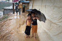 Children smile as they shelter from the rain in Balukhali-Kutupalong, a refugee camp sheltering over 800,000 Rohingya refugees, in Cox's Bazar, Bangladesh, June 23, 2018. The biggest refugee camp in the world is battling the onset of the monsoon rains. Humanitarian organisations on the ground and the Bangladeshi government are working hard to minimise the risks from landslides, flash floods, water born diseases and ultimately, loss of life. Thousands are facing dire circumstances as the conditions in the camps are expected to dramatically worsen with the onset of the heavy rains. © UNICEF/Bangladesh/Modola18 The biggest refugee camp in the world is battling the onset of the monsoon rains. Humanitarian organisations on the ground and the Bangladeshi government are working hard to minimize the risks from landslides, flash floods, water born diseases and ultimately, loss of life. Thousands are facing dire circumstances as the conditions in the camps are expected to dramatically worsen with the onset of the heavy rains.
