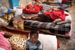 A child sits on a mattress laid on the floor of the women's section of the Al-Nasr detention centre in Zawiya, Libya, Sunday 20 August 2017. Libya is a country in turmoil. Since 2014, security is precarious, living is hard, and violence is commonplace. The country is riven with militias in conflict with each other or Government forces. Thousands of children and women hoping to reach Europe travel from Africa and the Middle East to the sea in Libya. They endure exploitation, abuse, violence and detention. As of June 2017, the International Organization for Migration identified 390,198 migrants in Libya, 11% of which are women and 7% are minors. Children and women making the journey live in the shadows, unprotected, outside the law, and reliant on smugglers. An estimated 34 detention centres have been identified in Libya. The Libyan Government Department for Combatting Illegal Migration runs 24 detention centres. They hold between 4,000 and 7,000 detainees. Armed groups hold migrants in an unknown number of unofficial detention centres. The international community, including UNICEF, only has access to some of the Government run detention centres.  Women interviewed by UNICEF reported harsh conditions with detainees suffering from the intense heat in the summer and cold in the winter. The detention centres are extremely overcrowded with as many as 20 migrants crammed into cells not larger than two square meters for long periods of time. This results in significant adverse health outcomes including the loss of hearing and sight, and extremely challenging psychological challenges. The militia run detention centres are labour camps, farms warehouses and makeshift prisons run by armed groups. The thousands of migrant women and children incarcerated in the militia run detention centres face violence, sexual exploitation, overcrowding, starvation and abuse. Reports by the United Nations Support Mission in Libya, and the Office of the High Commissioner for Human Rights p