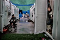 ギリシャの難民キャンプで、家から顔をのぞかせるシリア難民で18歳のアズハル・カリルさん。(2017年3月撮影)