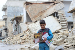 On 16 January 2017 in the Syrian Arab Republic, a child carries manuals distributed by UNICEF volunteers in the area following an informative session on identifying and reporting unexploded objects in Al- Sakhoor neighbourhood of East Aleppo.   UNICEF-supported volunteers are going door-to-door to talk to children, adolescents and parents about the risk of remnants of war. Since last November, more than 80,000 people have received life-saving information through house visits, awareness sessions, recreational activities for children and informative magazines and flyers detailing steps to identify and report these objects.   After fleeing months of fighting and attacks in East Aleppo, families returning to their partially-destroyed houses are faced with new dangers. The widespread presence of Unexploded Explosive Ordnance (UXO) in the area is exposing children to new life-threatening risks. In east Aleppo city, six children died in December when they were playing with unexploded remnants of war. Many more were injured.   UNICEF is urgently providing mine risk education for children and their families as they return to potentially dangerous areas.  UNICEF-supported partners and volunteers are going door-to-door to talk to children, adolescents and parents about the risk of remnants of war. Since last November, more than 80,000 people have received life-saving information through house visits, awareness sessions, recreational activities for children and informative magazines and flyers detailing steps to identify and report these objects.