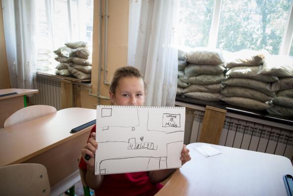 家の所在地を絵で説明してくれたミーシャ君。家は2つのチェックポイントに挟まれ、近くには「地雷危険」の看板が。