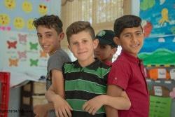 ユニセフが支援するマカニ・センターで、友人とポーズをとるアブドゥル・カディル君(中央)。 (ヨルダン・イルビド)
