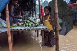 浸水したバングラデシュ・コックスバザールの難民キャンプで、野菜を買い求める8歳のハレマちゃん。 (2018年6月撮影)