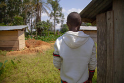 "On 14 August 2018, 'Dieudonne' [not his real name], a thirteen year old boy who lost eight members of his immediate family to Ebola, stands in Ebola-affected Mangina, North Kivu, the Democratic Republic of the Congo (DRC).  ""There were eight of them and they are all dead,"" says Dieudonné*, a young 13-year-old boy living in Mangina, the Democratic Republic of the Congo, where 27 cases of Ebola were recently confirmed.  It all started when Dieudonné's mother fell ill and died. ""When we buried Mum, the family was next to her body,"" the young boy explains. ""Soon after, everyone began to have headaches and diarrhoea.""   When his big sister was admitted to the Ebola treatment centre, Dieudonné stayed in the little family home alone, the same house that was the starting point of all his hardship. ""Everyone who entered our home fell sick,"" the boy recalls. At only 13 years of age, Dieudonné has lost all his bearings, all the people that he loved and on whom he could count. ""I don't have anyone who can take care of me anymore,"" sadly explains the young boy, who does not know if his sister will survive the disease. Dieudonné is one of 53 children orphaned by Ebola that UNICEF has identified in the east of the DRC. He currently benefits from psychosocial, material and dietary support. Dieudonné was also vaccinated against the disease a few days ago. The young boy does not what his future will be. ""I have to continue to live but I do not know how I will make it,"" he explains. ""This is serious."" Following the 1 August 2018 announcement by the Government of the Democratic Republic of the Congo (DRC) of a new Ebola Virus Disease (EVD) outbreak in North Kivu, UNICEF has mobilized its teams to help contain the spread of the disease and protect children. The impact of an outbreak on children can be far reaching. It's known from earlier outbreaks in the DRC as well as in West Africa that children can be affected in various ways. Children ca"