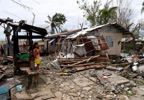 台風によって壊れた自宅のそばに立つ女の子。(2018年9月16日撮影)