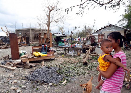 大型台風マンクットによって自宅を破壊され、1歳の娘を抱いてたたずむ母親のゴンザレスさん。
