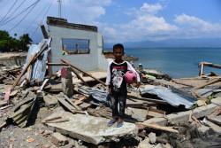 津波で破壊された自宅の前に立つ、10歳の男の子。(2018年10月3日撮影)