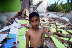 スラウェシ島のパルで、津波によって破壊された建物の前に立つ7歳の男の子。(2018年10月8日撮影)