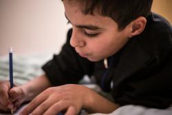 シリアから逃れ、現在生活を送るカナダの自宅で算数の宿題をするバゼル君(11歳)。(2016年12月撮影)