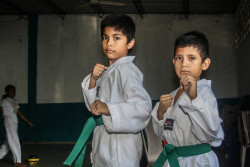 "San Marcos, San Salvador, El Salvador, Tuesday 23rd September  The municipality has made available a building for sports clubs to use, including a Tae Kwon Do club. Lessons run throughout the week and are for about 120 children.  Grandmother Haydee Bernal de Acevedo brings her grandsons: 11 year old Yahir Acevedo and 9 year old Gael Eduardo Acevedo at the Tae Kwon Do club.   She said she brings her grandsons here mainly to keep them away from trouble.  ""It gives them knowledge and improves their self-esteem"" ""It's very easy for boys to be influenced by gang members"" They have been coming for 4 years and she said it's working. ""The main difference in the boys is that they get congratulated and positive feedback for their achievements – they achieve different graded belts and are motivated to get more belts"".  GOOD QUOTE "" the boys now look up more to their teachers than to gang members""  ""They now know there are better people in the world (than gang members), their attitude is better and they want to be better at school and at home"". 11 yearr old Yahir says ""I love learning Tae Kwon Do. Before, we played soccer on the street."" Younger brother, 9 year old Gael also loves learning this martial art. Yahir is very proud to have his third belt, the green belt. The boys practise together and demonstrate some moves.   UNICEF has supported the municipality in reclaiming a range of public spaces through funding, technical expertise, data gathering and supply of equipment. The success of the initiative means that it can be scaled up and implemented more widely and attract further funding.  Violence is"