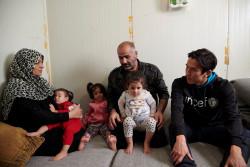 タレックさんの両親から、シリアからギリシャに逃れて来た時の様子を聞く長谷部選手。