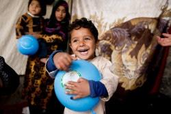 アフガニスタン南部で、ポリオの予防接種後に青い風船をもらって喜ぶ男の子。(2018年3月撮影)