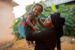 """On 5 July 2018 in Cameroon,       Antoinette and her daughter Natasha, 18 months, playing together at home in Adoum Soin village. In December 2016 in Cameroon, UNITAID in partnership with the Ministry of Health, UNICEF and implementing partners EGPAF and CHAI began implementing the new Point of Care Early Infant Diagnosis (POC EID) systems in Cameroon. Cameroon is among the 30 countries in the world that account for 89% of the total weight of HIV infections and the 10 countries that contribute to more than 75% of new pediatric infections. In 2017, only 46.3% of health facilities provided Early Infant Diagnosis (EID) to exposed children with 48.2% EID coverage.  Late diagnosis delays access to treatment for HIV-positive infants leaving them at a greater risk of death. The implementation of the new POC EID (Point of Care Early Infant Diagnosis) systems has the potential to promote an AIDS-Free Generation in Cameroon. In 2007, Antoinette found out her status when Martin her husband was hospitalized and tested HIV positive. She also tested positive. It was a very frightening time for them both. Antoinette says """"When I found out I was HIV positive, I thought that it was the end of my days. I was so afraid of this illness - the illness that kills people. I thought I was going to die and I thought my baby was going to be born with HIV too.""""  It was a very emotionally challenging time for her. """"I don't work. I have a small field which I farm. I work to feed my children and it makes me very proud. Even if it's hard work, I don't have a problem because I know that after work I'll be able to prepare a meal for them so they don't go to bed hungry."""" Fortunately on her journey, she met Rose Mekinda (peer counselor) at the Ebolowa District Hospital. Rose became a huge source of strength & advice for Antionette, and encouraged her to adhere to the PMTCT (Prevention of mother-to-child HIV transmission) process whilst pregnant. When Prisca was born, she was test"""