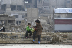 On 10 December 2018 in the Syrian Arab Republic, children sit on a fence near the central mosque in Douma, East Ghouta. Douma is home to the largest population in East Ghouta with more than 250,000 people living amidst large scale urban destruction, wide contamination with explosive remnants of war and limited access to essential services. UNICEF Executive Director Henrietta H. Fore is visiting the Syrian Arab Republic from 8-13 December 2018. In Douma, East Ghouta, just a few months after a seven-year siege was lifted, displaced families are beginning to return and the town's population is now estimated at 200,000. Many families have moved back into damaged buildings, and the threat of unexploded ordnance is pervasive. Since East Ghouta became more accessible UNICEF, through its partners, is providing a more comprehensive package of services including education, water and sanitation, health and nutrition and child protection.  Since May 2018, 23 children have been killed or injured in all of East Ghouta as a result of explosive remnants of war. There are 20 schools in Douma, all of them need varying degrees of rehabilitation. Such is the level of destruction in the town that a non-governmental partner organization set up an informal clinic, with UNICEF support, in the hall of a damaged mosque. The clinic, one of only six health facilities in the town, and offers vaccination and nutrition services as well as treatment for common childhood diseases.  In Hama, which saw violent fighting between rebels, government forces and extremists before falling back under government control, the UNICEF Executive Director visited a center where young boys and girls learn how to stand up against gender-based violence. On the last day of the trip, Fore visited Deraa, the birthplace of the Syrian uprising, and home to nearly 1 million people. Deraa has seen very high levels of displacement, with people moving frequently and for short periods of time, and putting additional strai