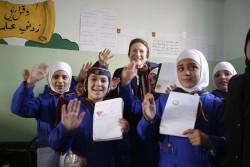 ヘンリエッタ・フォア事務局長と一緒に手を振る、小学校に通う女の子たちと。(2018年12月10日撮影)