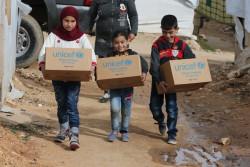 レバノン国内シリア国境近くの難民キャンプで、冬服などの支援物資を受け取った子どもたち。