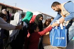 レバノン東部のベカー県で、冬服を含む支援物資をユニセフから受け取ったシリア難民の人たち。(2019年1月11日撮影)
