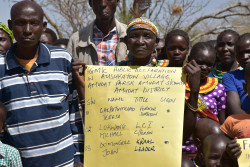 A former FGM cutter or surgeon together with other community members including children from Ausikioyon village in Amudat District,  hold a poster during the public declaration against Female Genital Mutilation (FGM/C) event in their village. This was prior to the commemoration of the national commemoration of the International Day of Zero Tolerance to Female Genital Mutilation held in Amudat District.