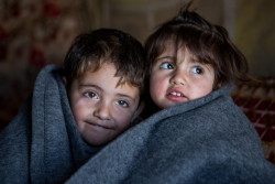 イラク北部の難民キャンプで、毛布にくるまる子どもたち。