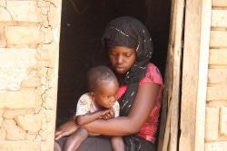 2歳の赤ちゃんを抱く母親のミリアさん。12歳で結婚を強いられ、妊娠したため、学校もやめなければならなかった。(ウガンダ)