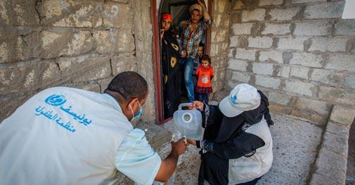 コレラ感染予防のための消毒剤を詰め替える即応チームのアミラさんとアーメッドさん