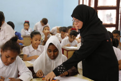 The teacher helps Fatima in the class.