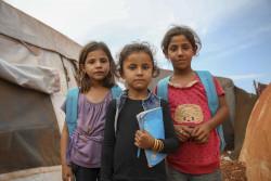 イドリブ郊外の一時滞在用キャンプで、7歳から14歳の350人の子どもたちが学ぶ仮設学校の前に立つ女の子たち。(2018年10月)