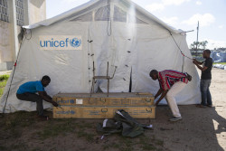 On 21 March 2019 in Mozambique, men set up a UNICEF distribution tent at the Samora Michel High School  in Beira. This tent will be used to distribute needed supplies to people that has been displaced by the floods caused by Cyclone Idai. Cyclone Idai has affected many people living in the Beira and surrounding areas of Mozambique. Thousands of people have been displaced. As at 17 March 2019, more than 1.5 million people – around half of whom are estimated to be children – have been affected by severe flooding in Malawi and Mozambique, with the numbers set to rise as Cyclone Idai moves west and the impact of the cyclone becomes clearer, UNICEF warned today. The tropical cyclone, which is carrying heavy rains and winds of up to 170km/h (106mp/h) made landfall at the port of Beira, Mozambique's fourth largest city, on Thursday 14 March, leaving the 500,000 residents without power and communications lines down. Across Mozambique, initial government figures estimate 600,000 people are affected of which 260,000 are children.  The cyclone moved across Mozambique to Zimbabwe over the weekend. Nearly 1.6 million people are estimated to live in areas that could be impacted by high winds and rainfall. While the full extent of the cyclone's impact is not yet clear, it is likely to include damage to schools and health facilities; damage to water and sanitation infrastructure; impeding access to safe water for affected communities; thereby bringing a heightened risk of water-borne diseases, destruction of people's homes, and increased protection risks, particularly for women and children. Since early March, flooding caused by the Tropical Cyclone Idai weather system has affected more than one million people and caused at least 145 deaths. UNICEF is working with partners to support the Governments of the affected countries to provide life-saving interventions to meet the needs of children and women impacted by the cyclone and floods. The response will include Health