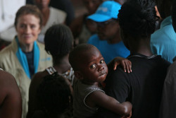 On 22 March 2019 in Beira in Mozambique, (centre front) a young boy looks toward the camera as (background left) UNICEF Executive Director Henrietta H. Fore speaks with internally displaced people as she visits a secondary school used to shelter evacuees from Cyclone Idai. Tropical cyclone Idai, carrying heavy rains and winds of up to 170km/h (106mp/h) made landfall at the port of Beira, Mozambique's fourth largest city, on Thursday 14 March 2019, leaving the 500,000 residents without power and communications lines down. On 23 March 2019, according to initial government estimates, 1.8 million people across the country, including 900,000 children, have been affected by the cyclone which slammed into the country last week. However, many areas are still not accessible and UNICEF and partners on the ground know that the final numbers will be much higher.  UNICEF is concerned that flooding, combined with overcrowded conditions in shelters, poor hygiene, stagnant water and infected water sources, is putting them at risk of diseases like cholera, malaria and diarrhoea. Initial assessments in Beira indicate that more than 2,600 classrooms have been destroyed and 39 health centers impacted. At least 11,000 houses have been totally destroyed. In Beira, Fore visited a school which had turned into a shelter for displaced families. Classrooms were converted into overcrowded bedrooms with limited access to water and sanitation. A UNICEF warehouse was severely damaged in the cyclone, causing the loss of essential supplies that had been pre-positioned before the cyclone made landfall. Cyclone Idai started as a tropical depression in Malawi, where it forced families from their homes into churches, schools and public buildings. Nearly half a million children are affected. After Mozambique, the cyclone moved to Zimbabwe where it caused significant damage to schools and water systems.  Children need to regain access to health, education, water and sanitation, and to heal from the