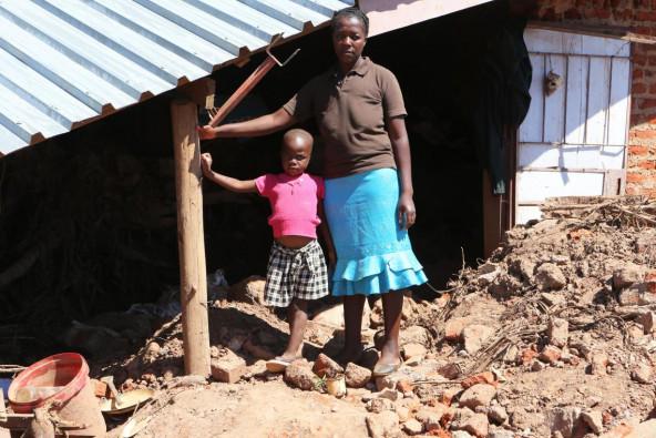 サイクロン「イダイ」によって破壊された自宅に前に立つ、プルーデンスちゃんと母親。